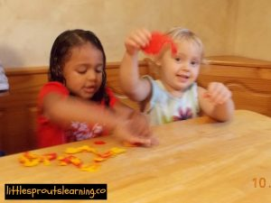 mixing red and yellow play dough to make orange