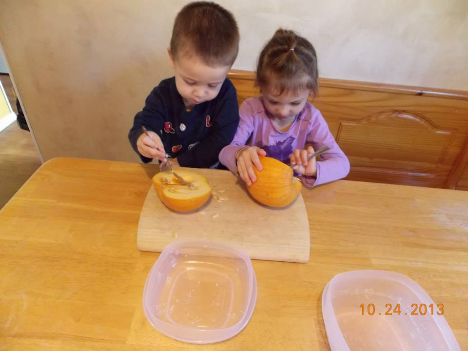Kids exploring pumpkins by scraping out pumpkin guts and seeds with a spoons