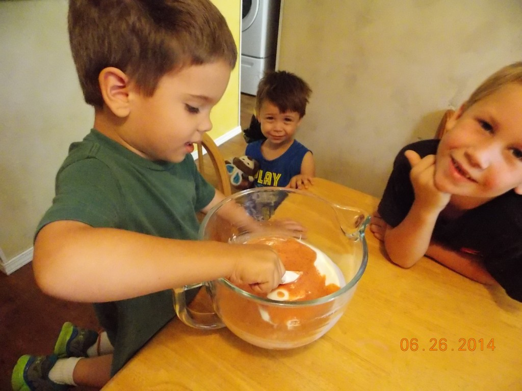 kids stirring pureed peaches into yogurt