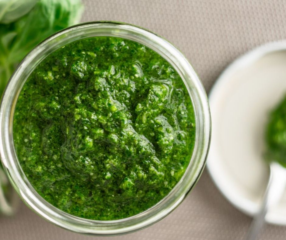 Basil pesto in a mason jar on the counter