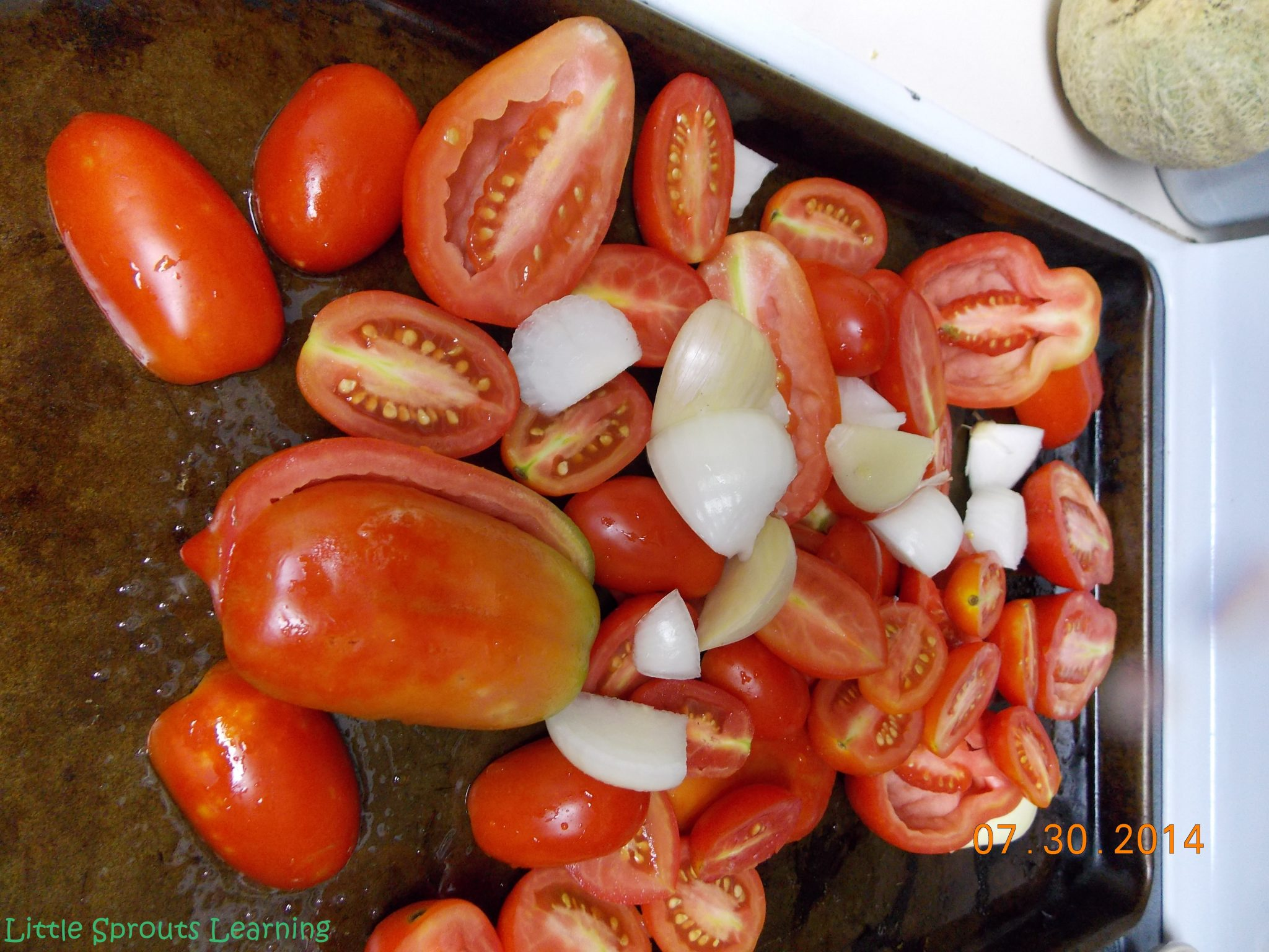 tomatoes cut in half on sheet pan with cloves of garlic and chopped onions for making roasted tomato sauce