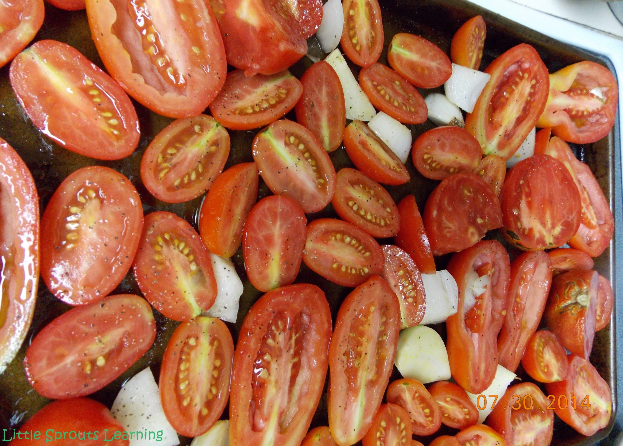 tomatoes, onions and garlic tossed in olive oil, salt and pepper on a sheet pan ready to go in the oven to roast.