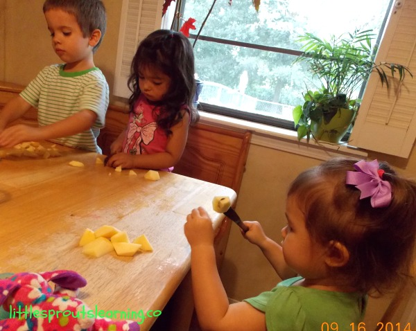 children using butterknives to cut apples into chunks