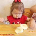 young child cutting apples into chunks with a butter knife