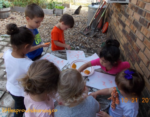 learning with pumpkins, kids doing pumpkin stamping with ink pads and paper on a table outside