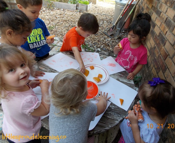 kids doing fall activities around a table with scraps of pumpkin flesh and ink pads, pumpkin stamping.
