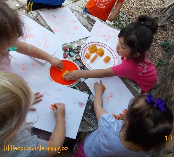 Kids stamping with pumpkin stamps with ink pads and paper. Pumpkin art preschool