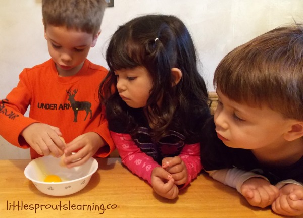 kids cracking eggs in a bowl