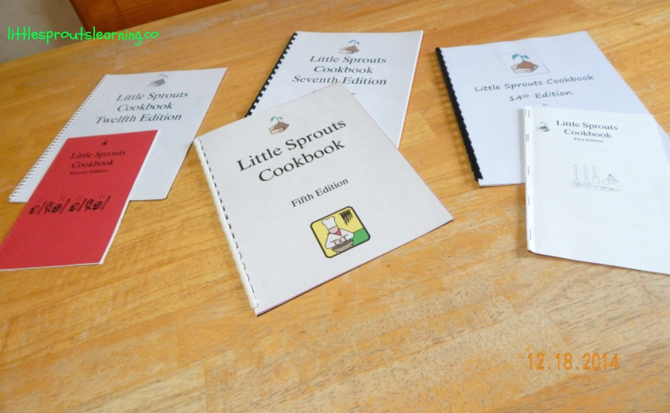 children's cookbooks arranged on a table, some stapled, some bound.