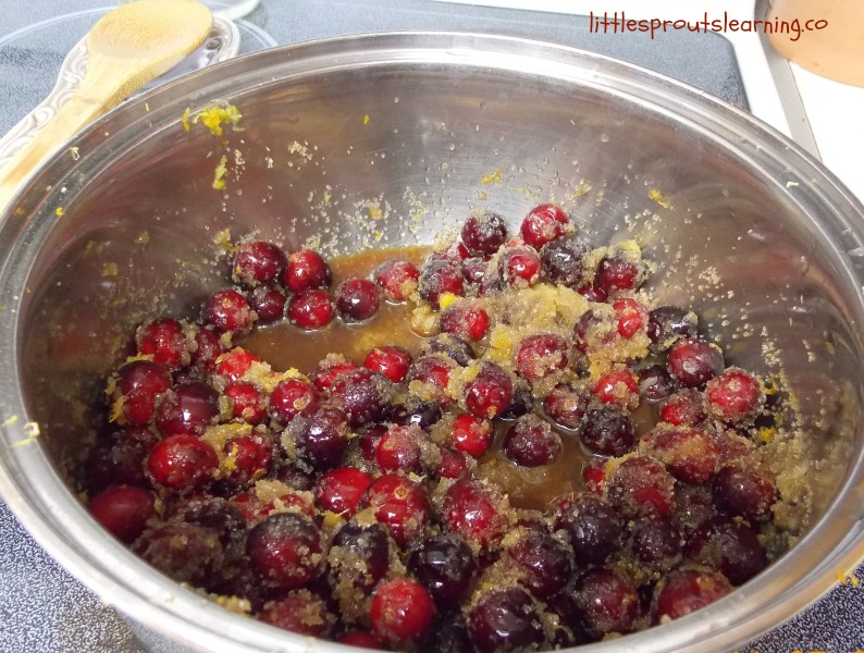 homemade cranberry sauce, pan of cranberry sauce with orange zest and sugar on the stove