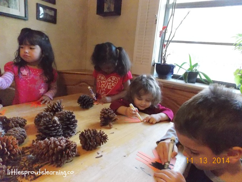 daycare kids doing activities at the table with hand prints, markers and pinecones