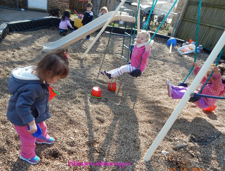 Kids playing outside, some swinging, some digging in pea gravel, some playing with a shopping cart, the importance of play in early childhood settings.