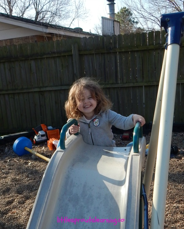 child enjoying play in early childhood setting by climbing up a slide outside. Shes smiling and having fun.