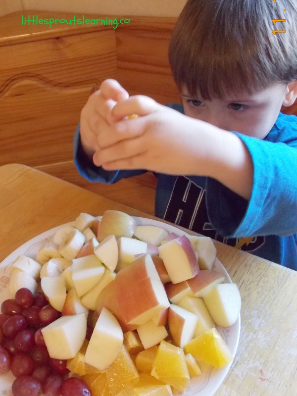 Yummy, fun, healthy fruit kabobs-cooking with kids. Child squeezing lemon juice on a plate of cut up fruit for fruit kabobs, bananas, oranges, grapes and apples.
