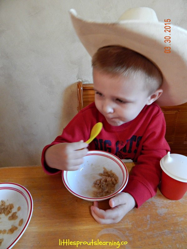 child eating a bowl of oatmeal for breakfast at the table wearing a cowboy hat