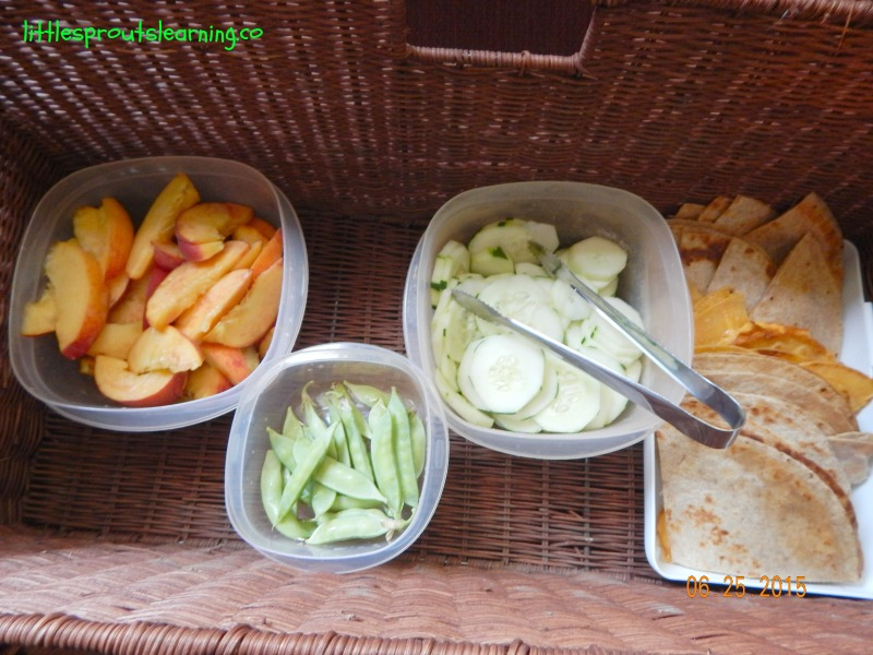 picnic basket full of cut up fruits and vegetables
