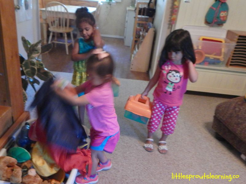 kids cleaning up, picking up toys and putting them in the basket.