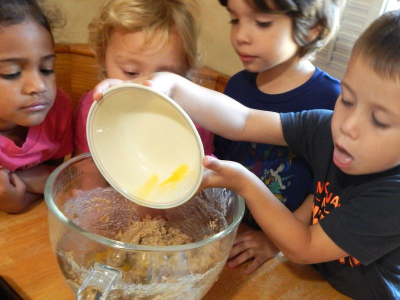 lesson plans for preschool, cooking with kids, four kids at the table with a bowl of batter, one is pouring in an egg