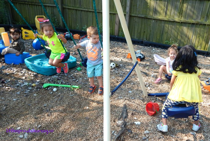 daycare lesson plans, outside play, a child sitting on a toy, two on swings and two on a teeter totter