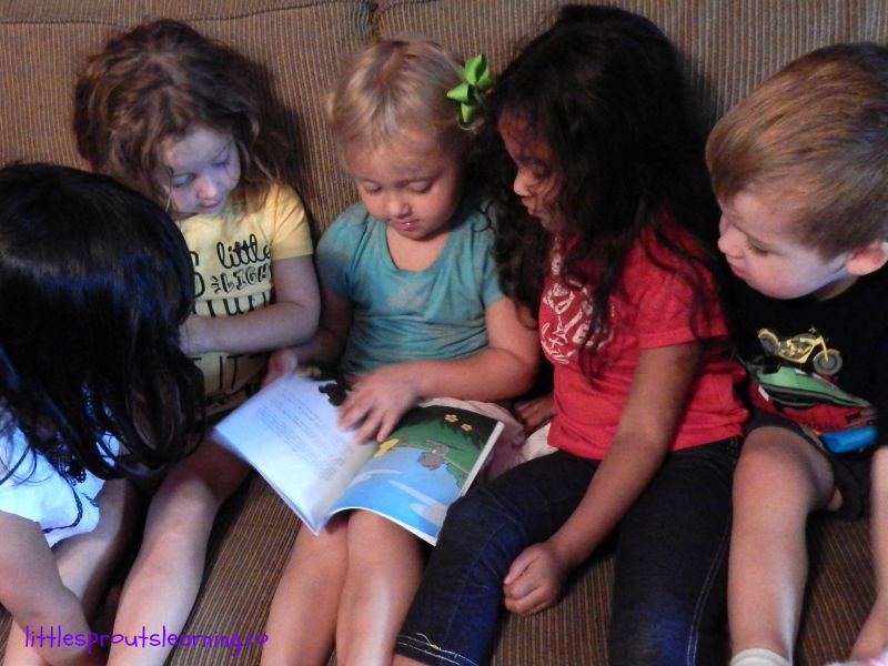 5 kids sitting on the couch looking at a book together, importance of reading to your child