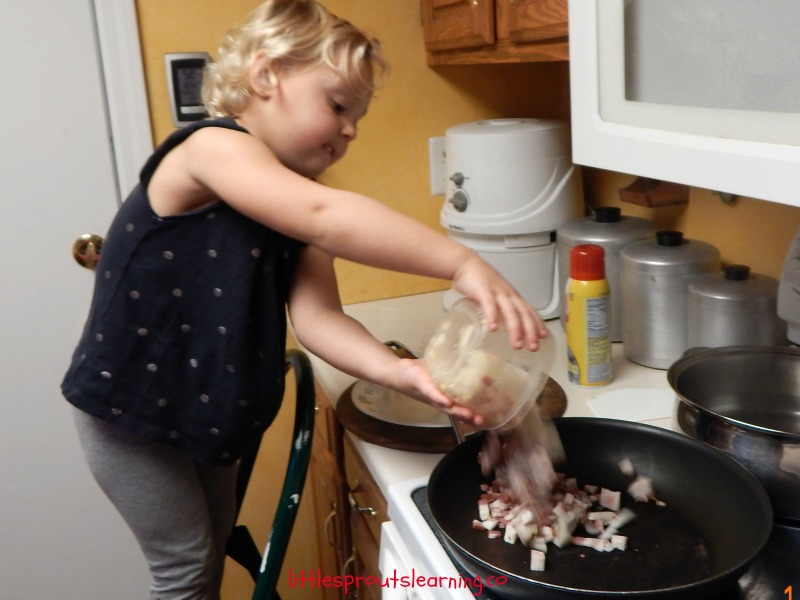Lotsa Pasta Recipe-Kids cooking classes. Child standing at the stove putting bacon in a skillet to brown.