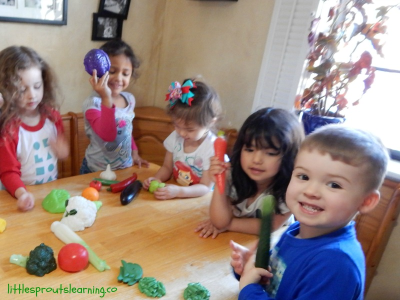healthy Snack Ideas for Kids, kids at the table with plastic fruits and vegetables playing a healthy food game.