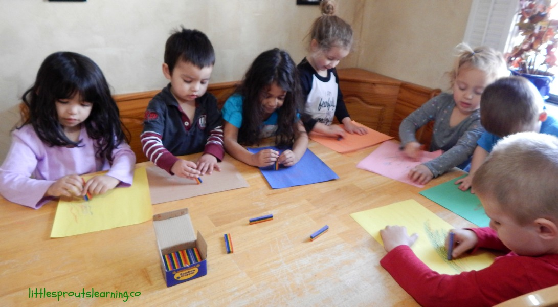 Daycare kids creating art with rainbow crayons and paper around a table