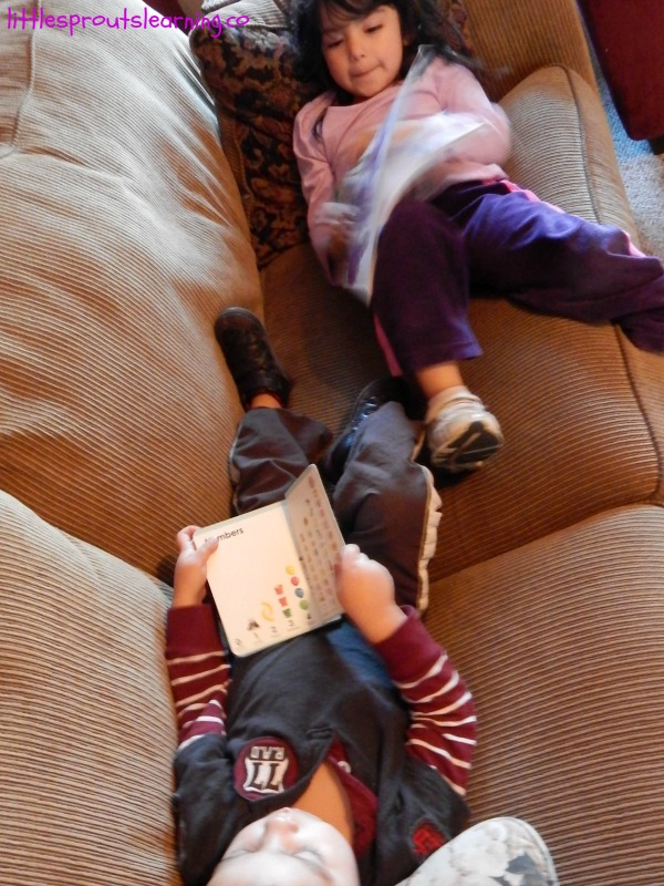 importance of reading for children, two kids laying on the couch with books.