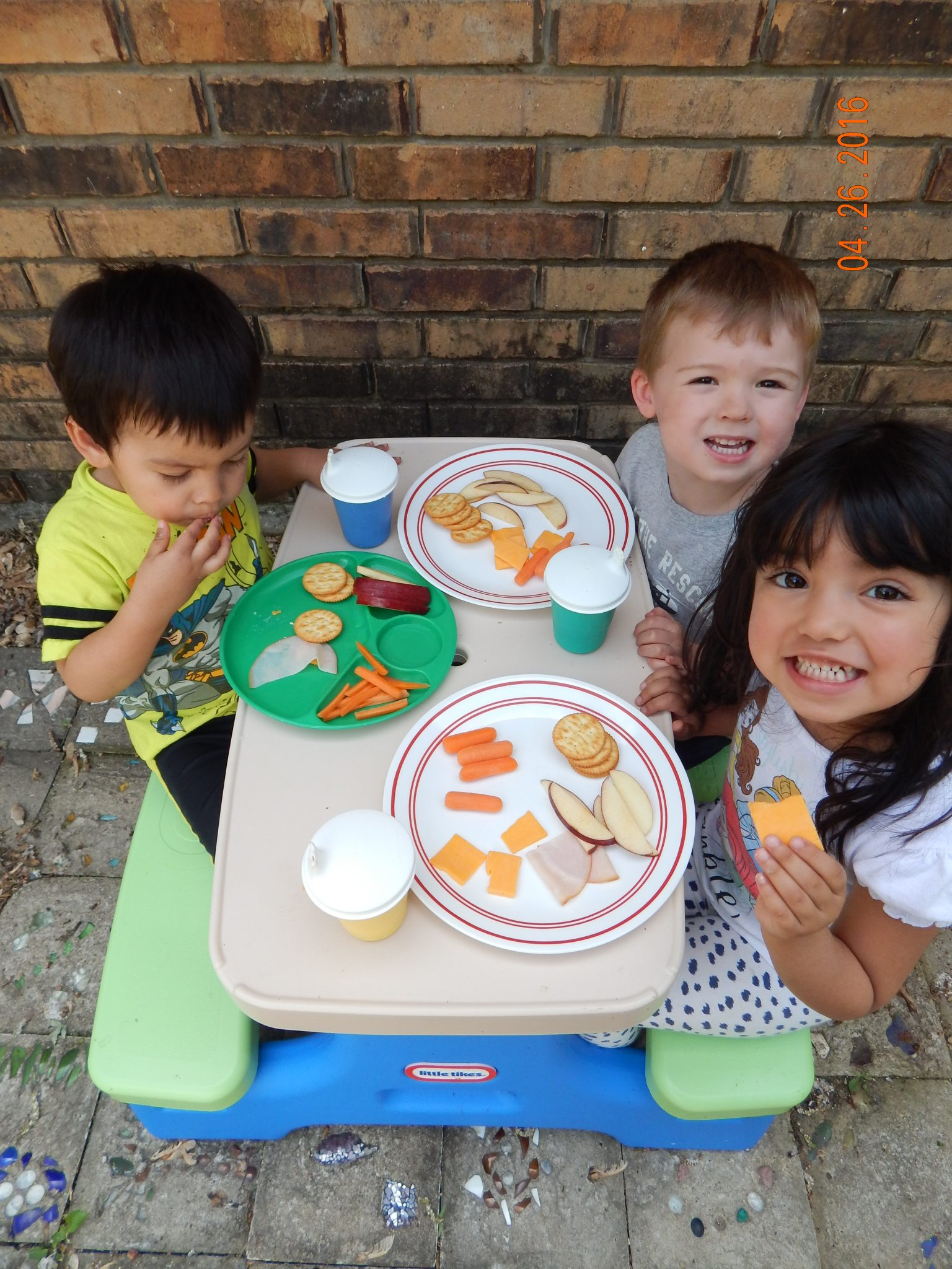 feeding toddlers healthy food for lunch, three kids sitting at a picnic table with plates of healthy food. They are eating and smiling.