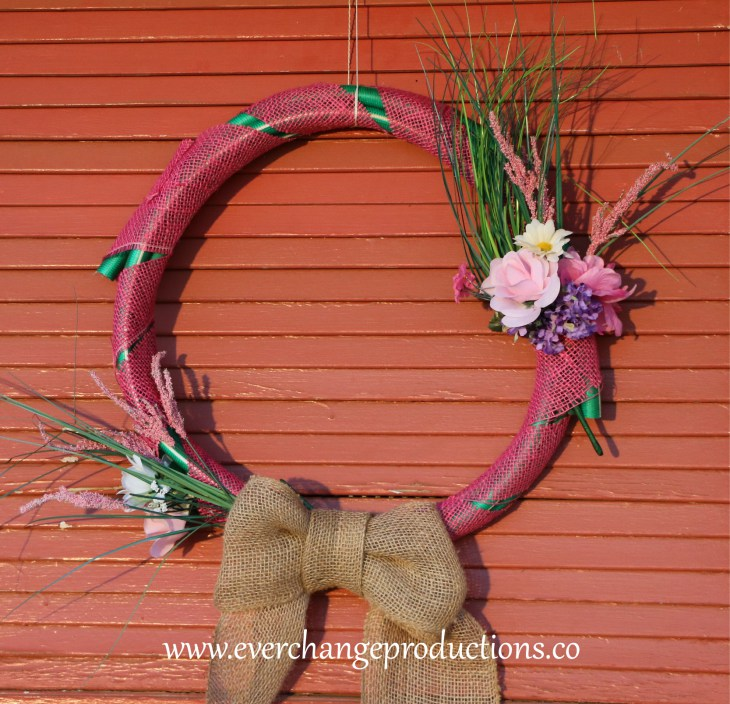 hose wreath made of upcycled hose, burlap ribbon, and decorated with flowers hanging on a door