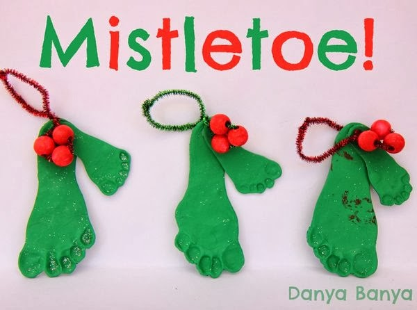clay footprint ornaments. Kid's food prints in green clay and stuck together with a pipe cleaner hanger and holly berries of pom poms, mistletoe ornament Christmas gifts for parents