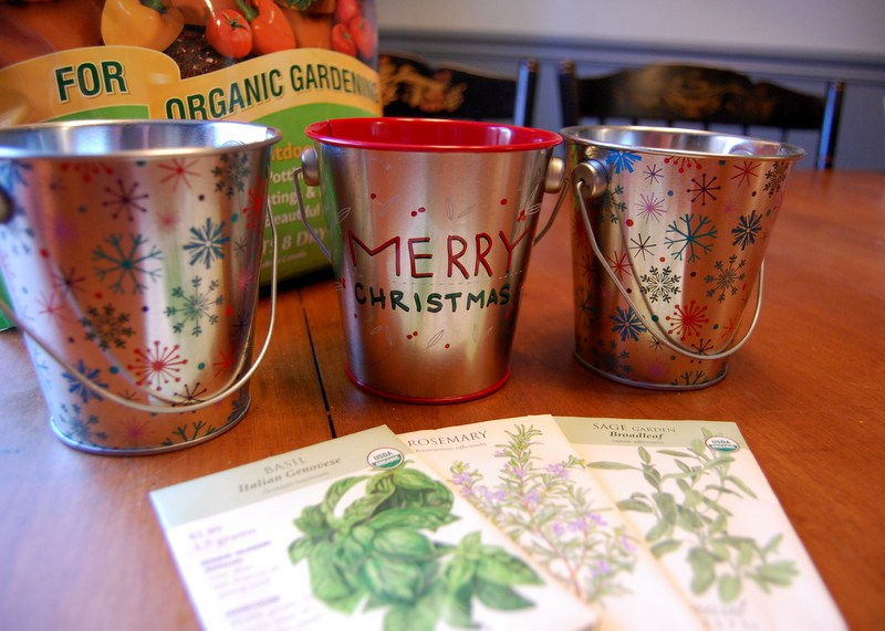 metal pails decorated with christmas decor with organic potting soil and seeds, homemade herb garden gift