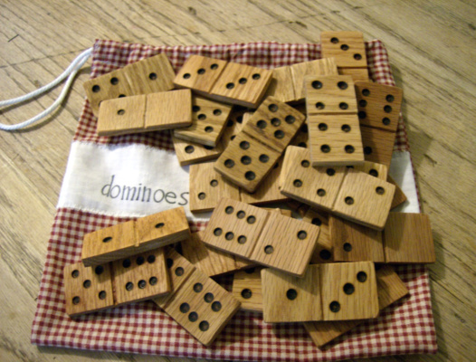 homemade wooden dominoes in a pile on top the bag