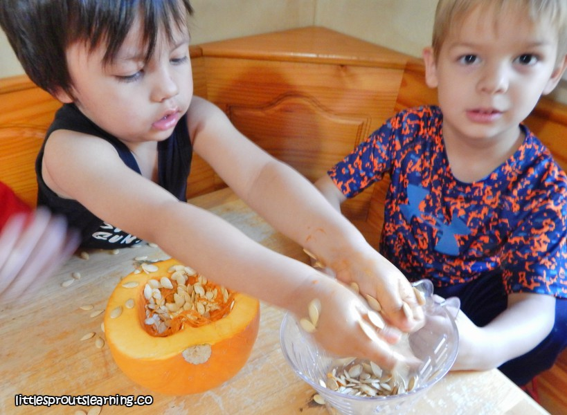 kids removing pumpkin goo from cut pumpkin