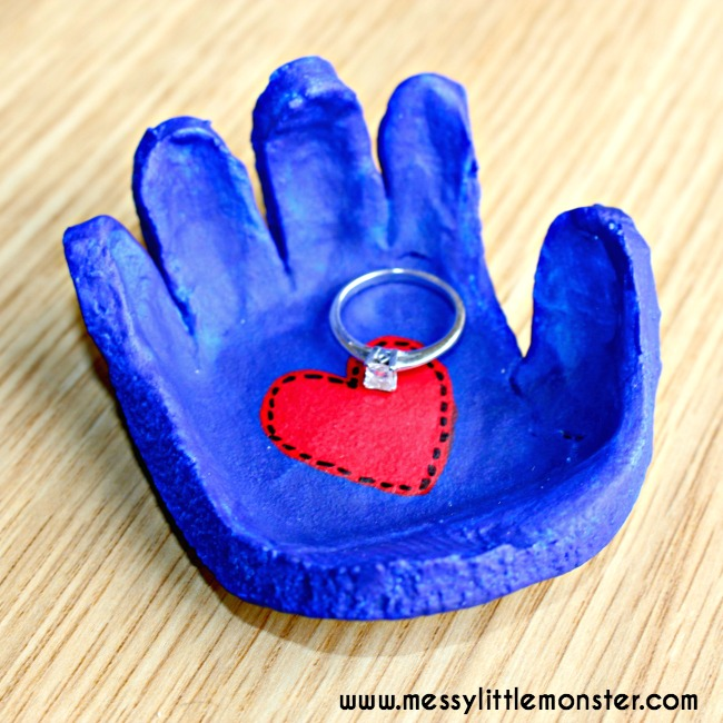salt dough dish in the shape of a child's hand. Painted blue with a red heart in the center and a ring in the dish, great christmas gift for parents from kids