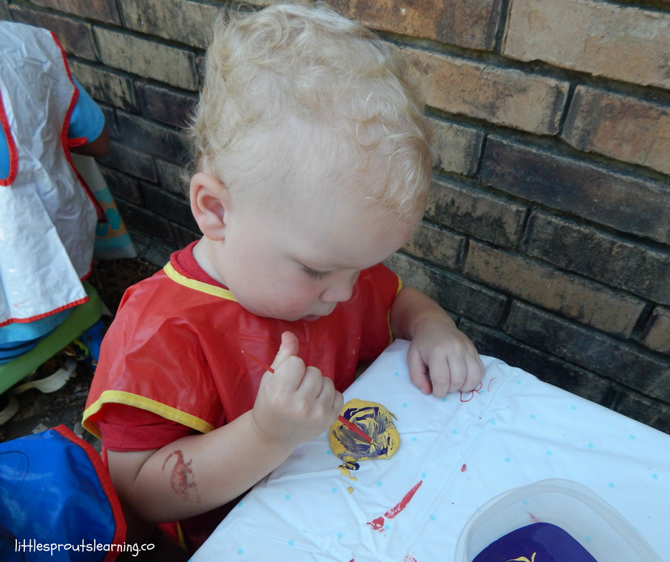 child painting garden rock