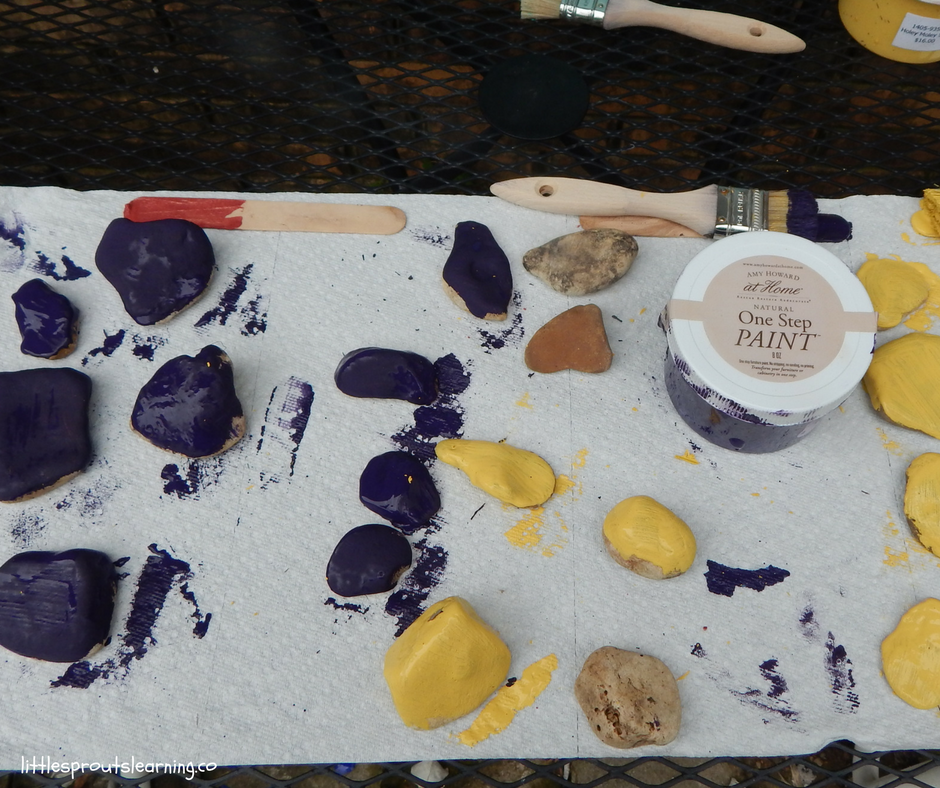 paints, paint brushes and rocks to paint for the garden