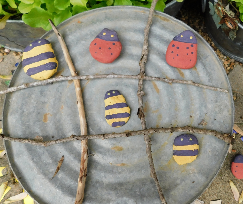 tic tac toe board with painted ladybug rocks and bee rocks