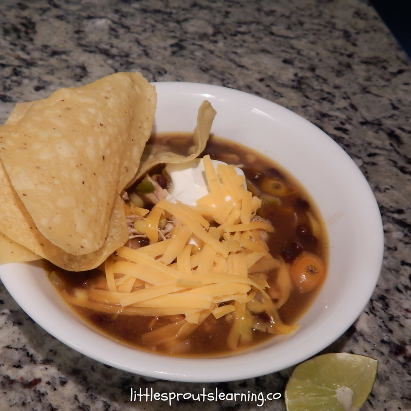 bowl of chicken tortilla soup on the counter with tortilla chips on the side and a lime wedge.