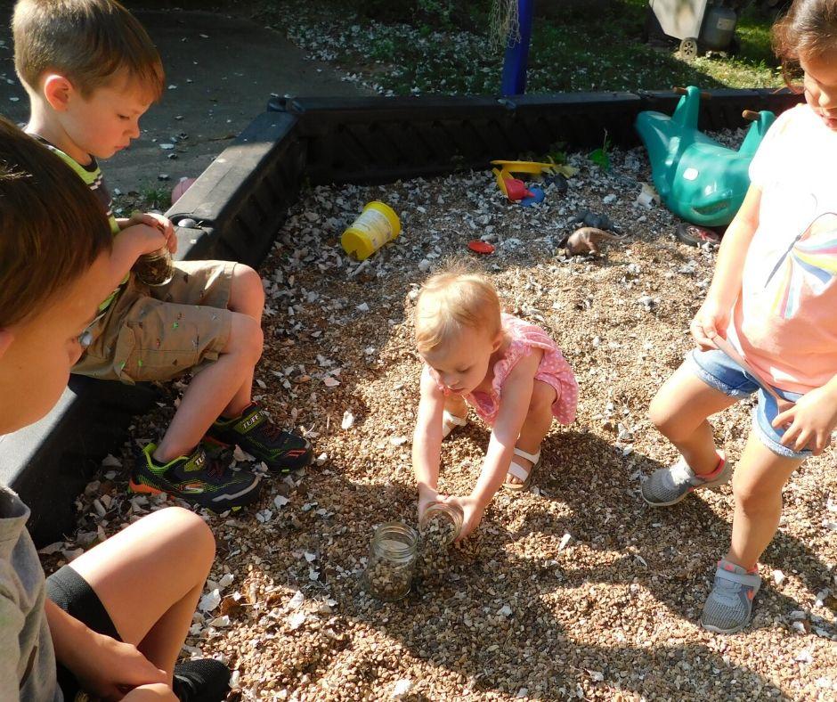 child filling jar with pea gravel to make diy terrarium