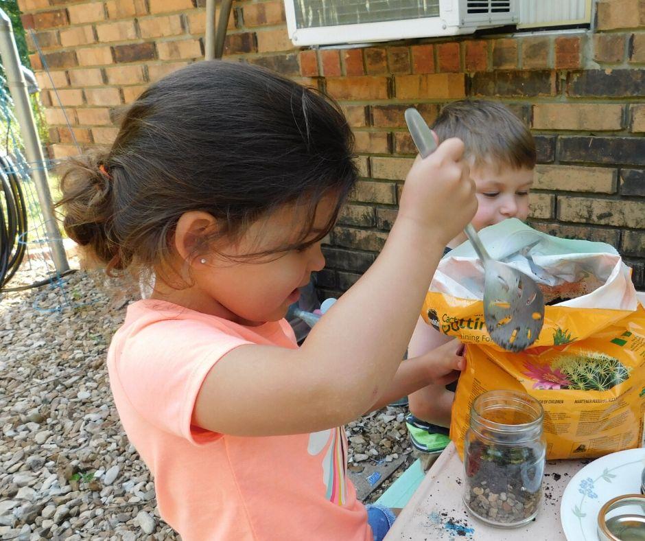 child filling jar with cactus soil in diy terrarium