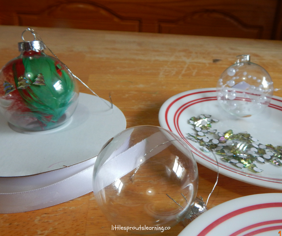 clear ornaments with feathers and pearls inside