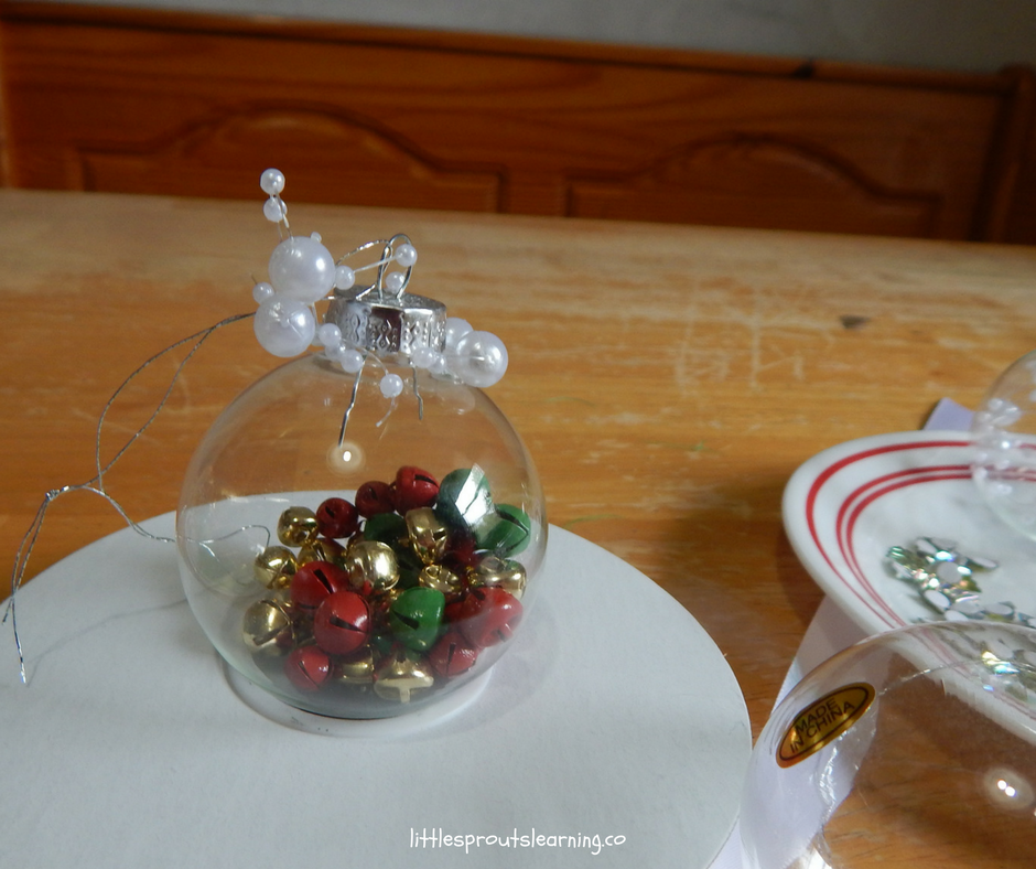 clear Ornaments stuffed with red, green and gold jingle bells and topped with pearls