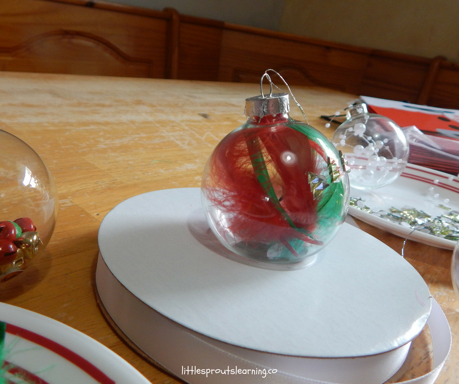 clear ornaments with feathers and ribbons inside, red and green