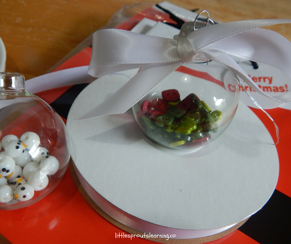 clear ornament with snowman head beads and another clear ornament full of red and green buttons and topped with a big white ribbon bow.
