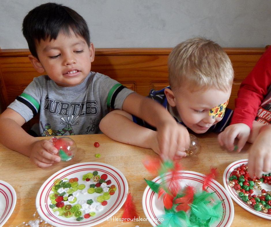 kids stuffing clear ornaments with pretty decorations like feathers, buttons, and tiny bells