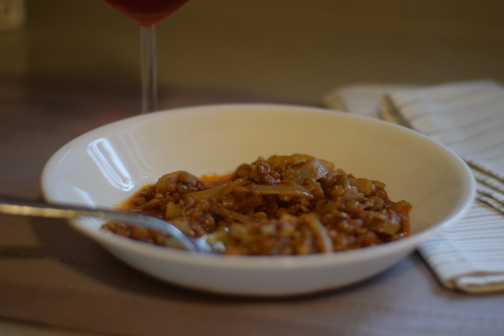 bowl of greek lentil soup with a spoon for quick easy dinner soup