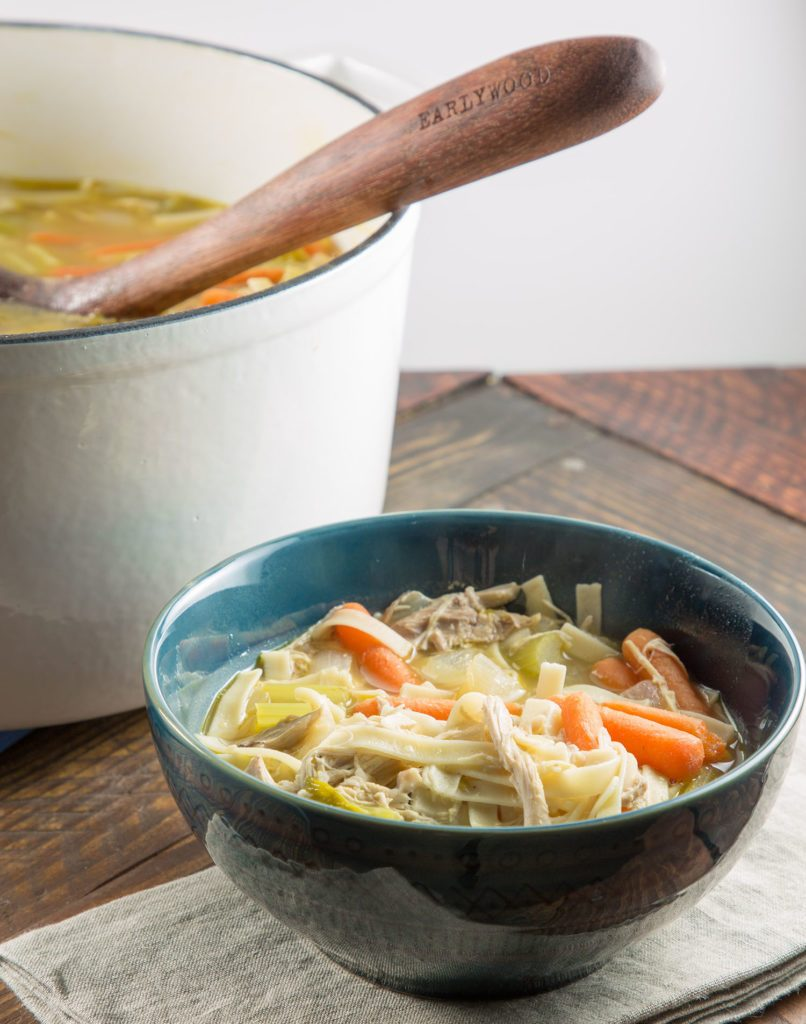 bowl of chicken noodle soup for quick easy dinner idea on a napkin next to apot of soup