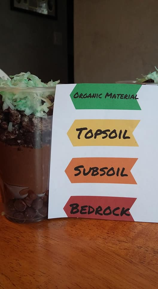 cup of snacks with different layers like the layers of soil in teh garden, organic material, topsoil, subsoil and bedrock