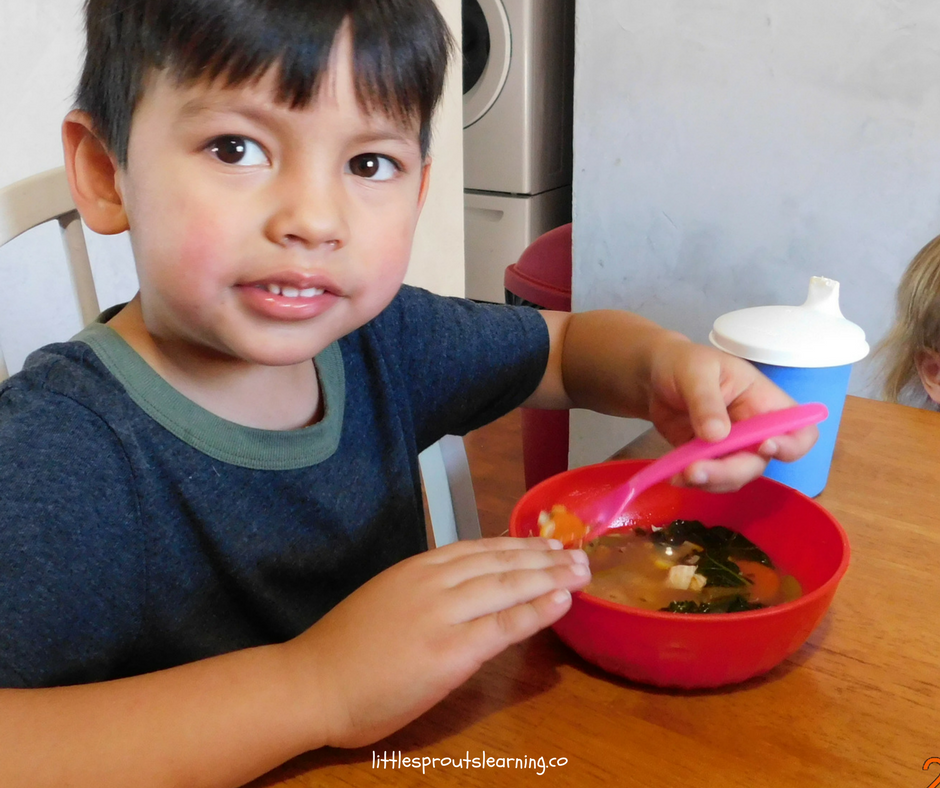 boy at the table enjoying friendship soup he made with his friends.